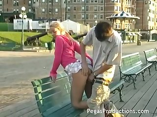 Naughty blond girlfriend Candy Kiss sucks a gumshoe outdoor and gets fucked on the bench