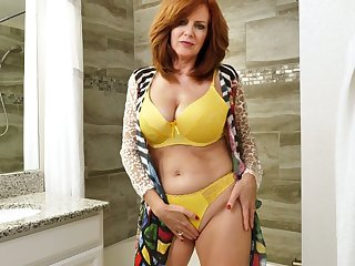 Red haired mature woman Andi James is enticing a shower and masturbating pussy